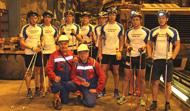Hiihtäjät ryhmäkuvassa kaivoksen uumenissa olevassa korjaamossa